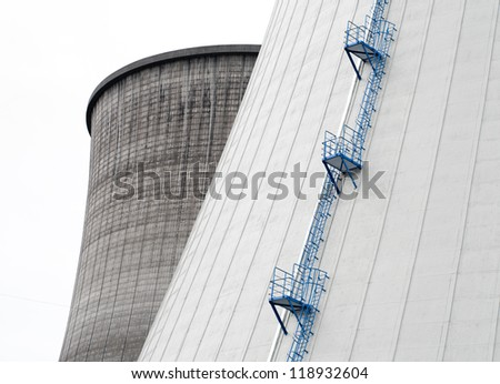 close-up of two cooling towers of a nuclear power plant with a blue staircase on it - stock photo