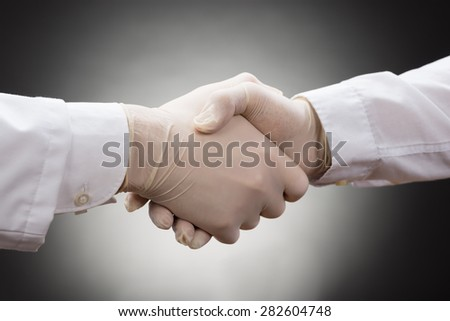 Close-up Of Two Doctor's With Glove Shaking Hand