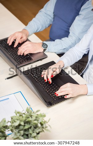 Close-up of two elderly businesspeople writing on computers - stock photo