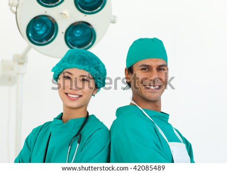 Close-up of two ethnic surgeons smiling at the camera - stock photo