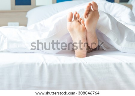 Close up of two feet in a bed.focus on feet