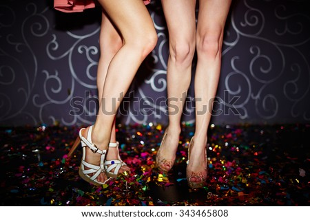 Close-up of two female legs dancing in night club - stock photo