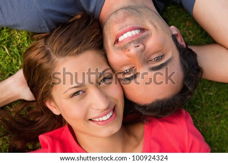 Close-up of two friends smiling while looking towards they sky as they lie head to shoulder with an arm behind their head on the grass - stock photo