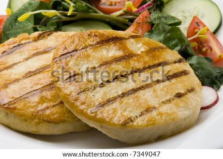 close up of  two grilled chicken hamburgers  with tomato, cucumber and spinach salad on white dish