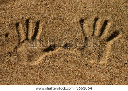 close-up of two hand imprints in sand - stock photo