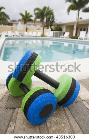 Close-up of two hand weights at the poolside - stock photo