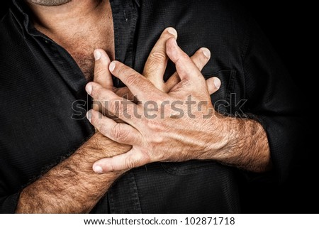 Close up of two hands grabbing a chest on a black background, useful to represent a heart attack or any sentimental concept - stock photo
