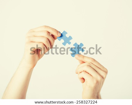 close up of two hands trying to connect puzzle pieces