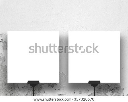 Close-up of two hanged square paper sheet frames with clips on weathered wall background