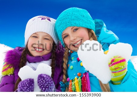 Close-up of two happy girls with heart made of snow, standing together outside in winter - stock photo