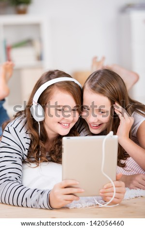 Close-up of two happy young teenage girls sharing headphones connected to a tablet to listen to music while laying on the living-room floor - stock photo