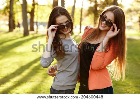 Close-up Of Two Happy Young Women Wearing Sunglasses - stock photo