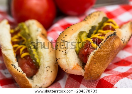 Close up of two hot dogs on red checkered napkin
