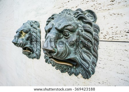 Close-up of two lion heads on wall