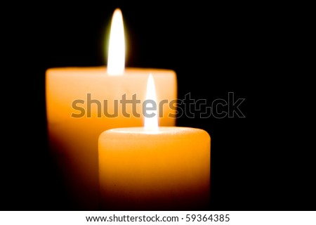 Close up of two lit white candles on black background. - stock photo