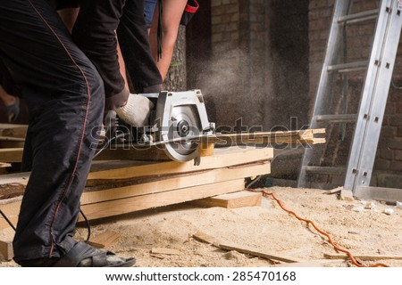 Close Up of Two Men Using Hand Held Power Saw to Cut Planks of Wood for Home Construction Leaving Piles of Saw Dust on Floor - stock photo