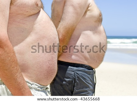 Close-up of two obesely fat men showing their bellies on the beach - stock photo