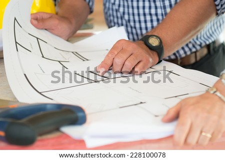 Close-up Of Two People Discussing Plan On Blueprint - stock photo