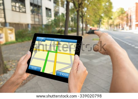 Close-up Of Two People Hands Using Gps Map Navigation On Digital Tablet - stock photo