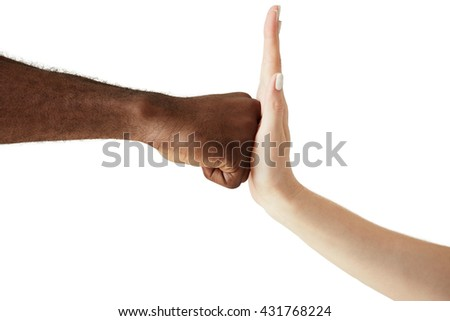 Close up of two people of different ethnicites and cultures holding hands in handshake showing respect, solidarity and cooperation. African man throwing a punch at the open palm of Caucasian woman - stock photo