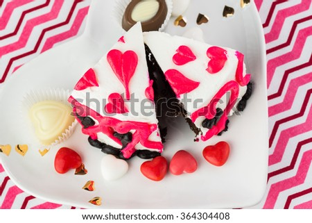 Close up of two pieces of chocolate cake, decorated for Valentines Day on heart shaped plate.