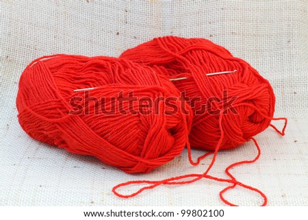 Close up of two red balls (clews) of yarn and knitting hook - stock photo