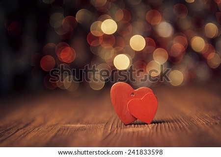 Close up of two red hearts on old wooden board against defocused lights - stock photo
