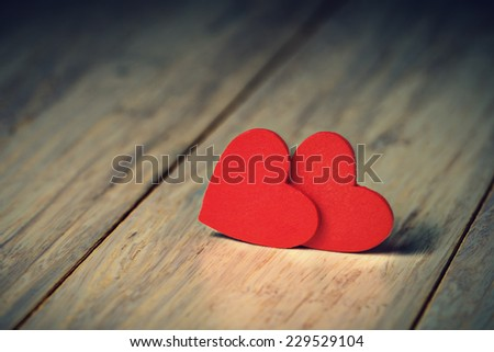 Close up of two red hearts on wooden table. - stock photo