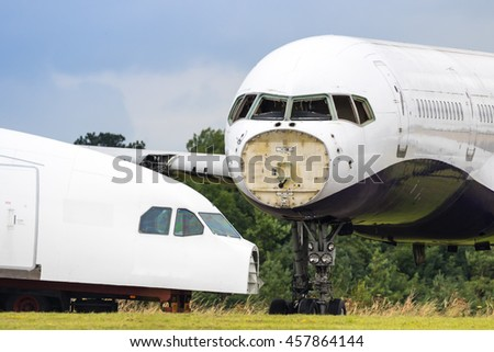 Close up of two redundant passenger airliners being dismantled in a field - stock photo