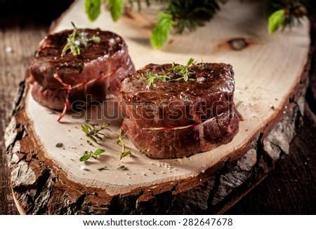 Close Up of Two Roasted Venison Steak Filets Seasoned with Fresh Herbs and Served on Rustic Wood Plank - stock photo
