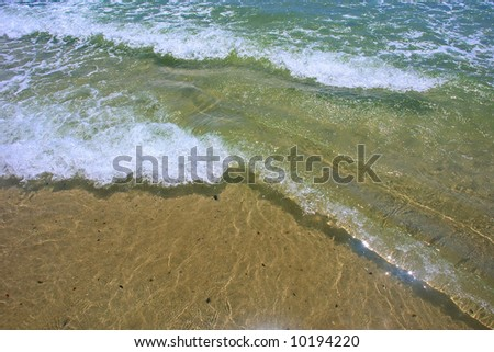 Close-up of two sea waves crossing on beach. Shot near Strand, Pringle and Bettys Bays, Western Cape, South Africa.