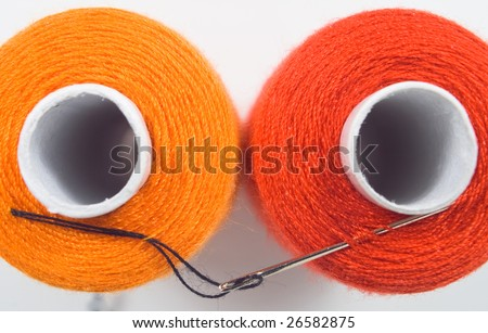 close up of two sewing spools with a needle