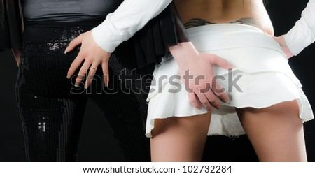 Close up of two sexy girls grabbing each others behinds on black background - stock photo
