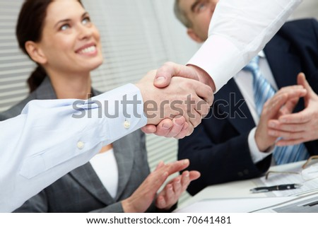 Close-up of two shaking hands against business team - stock photo