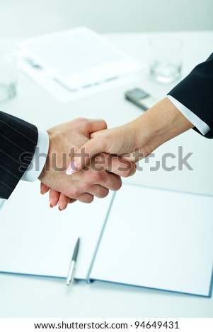 Close-up of two shaking hands with business documents on background