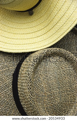 Close-up of two straw hats, one light yellow and the other dark brown