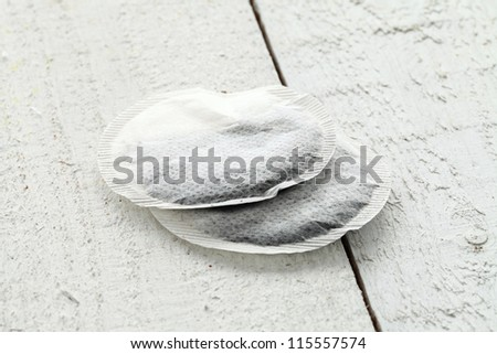 Close up of two teabags on wooden table - stock photo