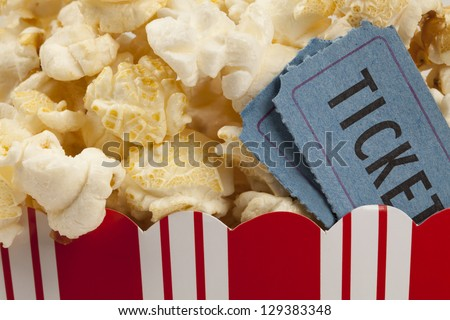 close up of two tickets stubs in a box of popcorn. Concept of movie time. - stock photo
