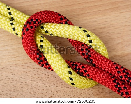 Close up of two tied ropes on a wooden background. - stock photo