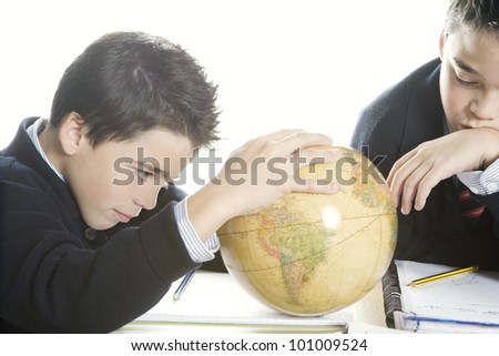 Close up of two twin brothers doing their geography homework, using a globe. - stock photo