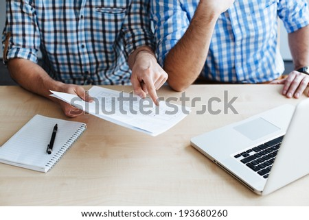 Close-up of two web designers discussing the layout of a website - stock photo