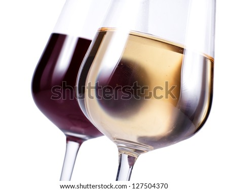 close up of two wine glasses with red and white wine isolated over white - stock photo
