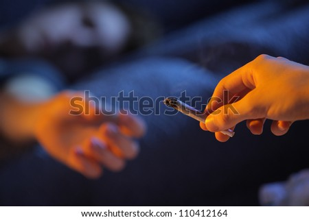 Close up of two young adults smoking a joint - stock photo