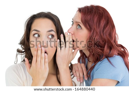 Close-up of two young female friends gossiping over white background