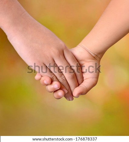 Close up of two young girls holding hands