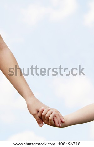 Close up of two young girls holding hands against the blue sky. - stock photo