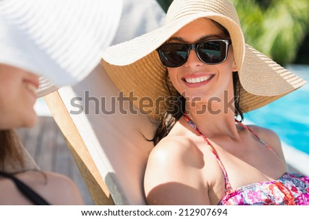 Close up of two young women wearing hats by swimming pool - stock photo