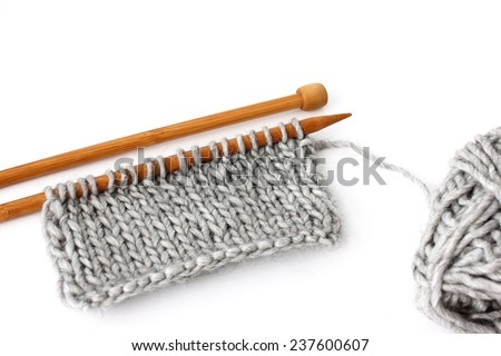 Close-up of unfinished knitting project with grey skein and wooden needles - isolated on white
