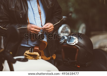 Close up of unrecognizable adult man with film camera at vintage motorbike with helmet