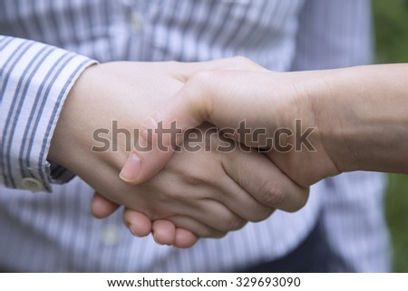 Close up of unrecognizable business people shaking hands.